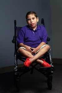 Boy with purple shirt sitting in his wheelchair