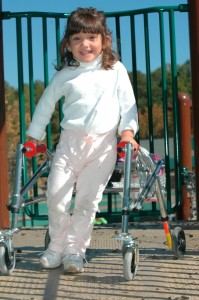 Young girl with a walker playing on an accessible playground